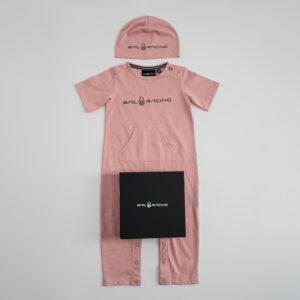 En kortärmad rosa body med matchande mössa båda med texten Sail Racing i svart. På bodyn ligger en svart presentlåda
