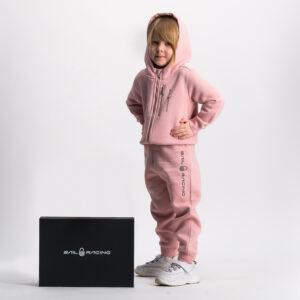 Flickan i den rosa Sail Racing träningsoverallen står bredvid en svart presentlåda med texten Sail Racing i vitt