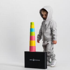 Pojken i den grå Sail Racing träningsoverallen tittar på ett färgglatt torn som står på den svarta presentlådan med Sail Racing i vitt