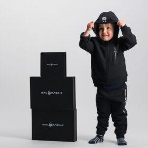 pojke i en svart träningsoverall från Sail Racing. Han håller i huvan med händerna. På golvet står ett torn av presenter i svart med texten Sail Racing på